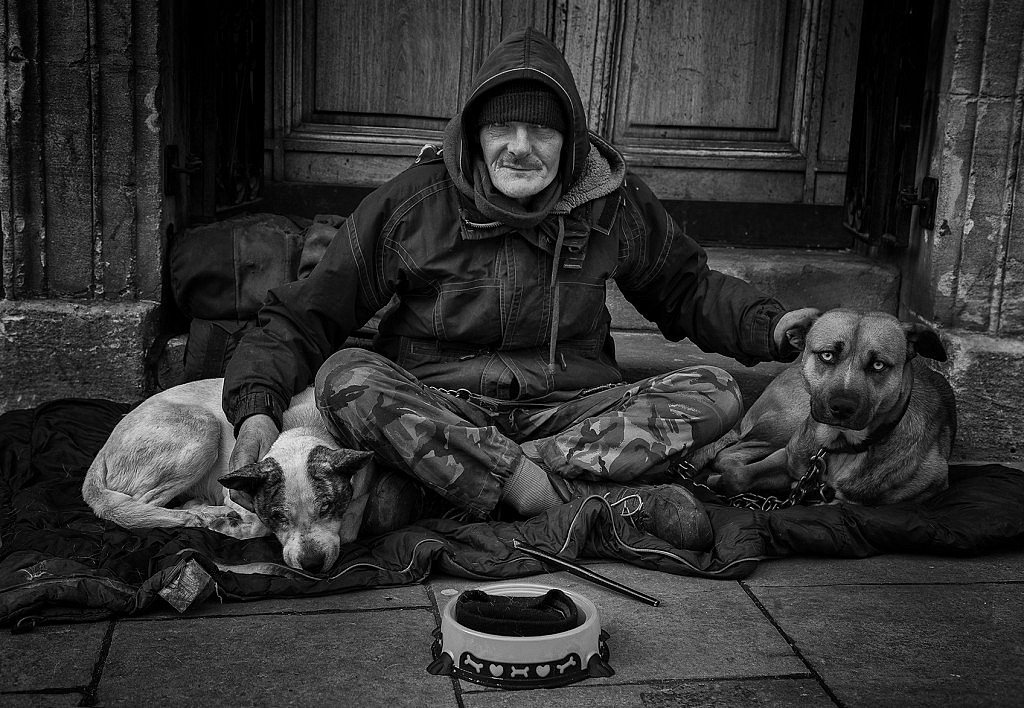 A street person on the streets of Bath with his two companion dogs