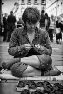 sitting girl with paper flowers- street photography from Bath