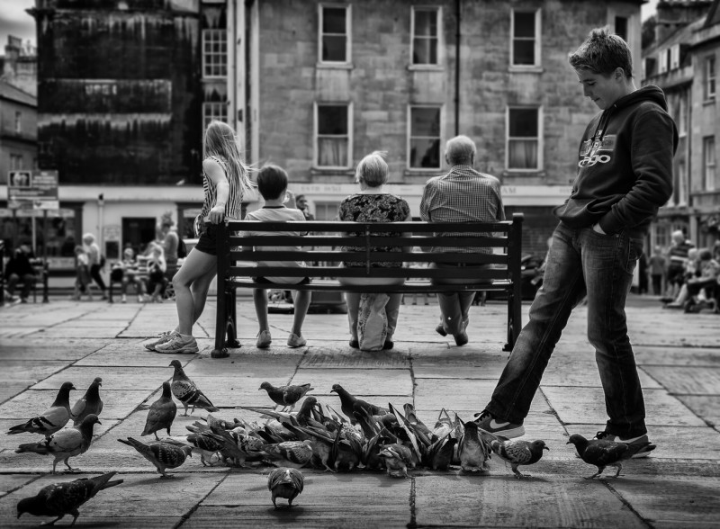 boy kicking at pigeons - UK street Photography